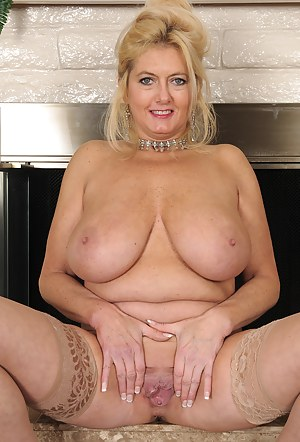 Busty and elegant 47 year old Tahnee Taylor pising by the fireplace