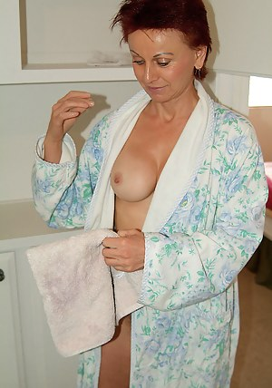 Redheaded MILF with a hairy pussy leaves her bathrobe undone