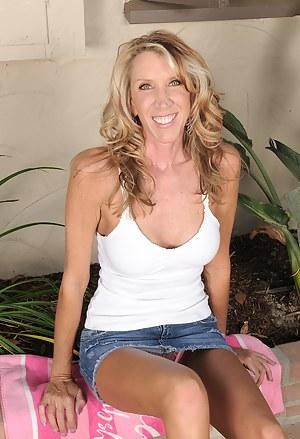 Busty blonde Brinn Hunter slips off her denim skirt and spreads wide