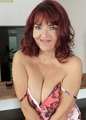 Busty older redhead Natalia spreads mature pussy.