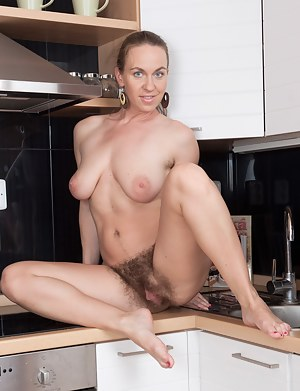Erin can think of a few things that are more fun than cooking in the kitchen. She is one hairy woman and likes to show it off! She strips and spreads out on the counter top showing her hairy pussy!