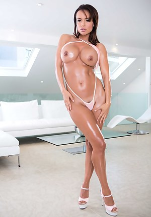 Oiled-up brunette in an elaborate barely-there get-up gets oiled up and lets a hung guy bury his cock deep inside of her asshole.