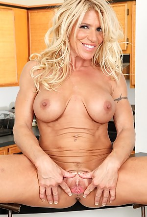 Busty blond cougar Gina West masturbating on the table.