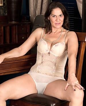 Older office babe Kaysy strips naked on her desk.