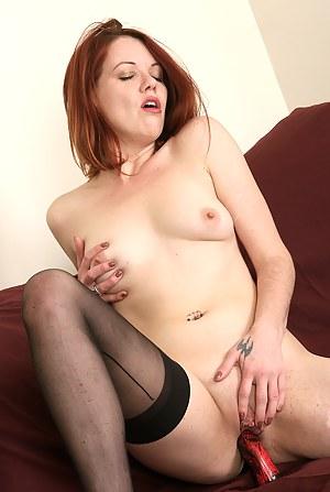 Redheaded MILF Lilla Katt pushes a red dildo deep into her vagina