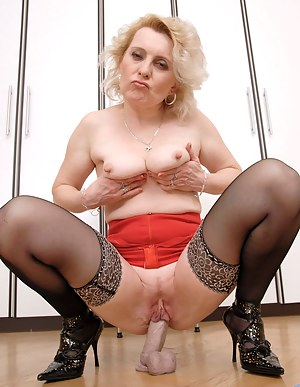 Mature Anilos woman pulls up her red skirt and bangs her seasoned cougar pussy with her big dildo