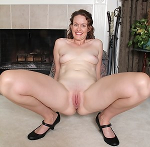 Older redhead Ajia Simpson spreads trimmed pussy.