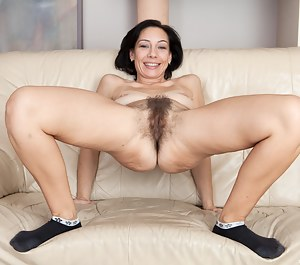 Eva pulls her panties up between her pussy lips and her long pussy hair extends outside her undies. With nothing but her socks on, this natural girl lifts her leg to play with her very hairy muff.