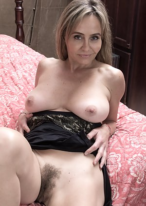 On her bed, Sarah Michaels is elegant and sexy. Her black lingerie slides off her mature body and she lays back. Naked on her bed, she has a full hairy pussy and she tugs on her hairy cunt to show it off.