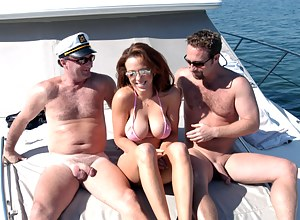 Wonderful cutie with big tits gets seduced by two handsome fellows while walking down the beach for a threesome sex on their luxury boat.