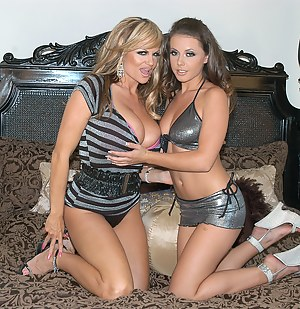 Kelly and Penny make each other cum on the bed.